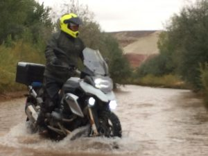Man crossing a river on a motorcycle