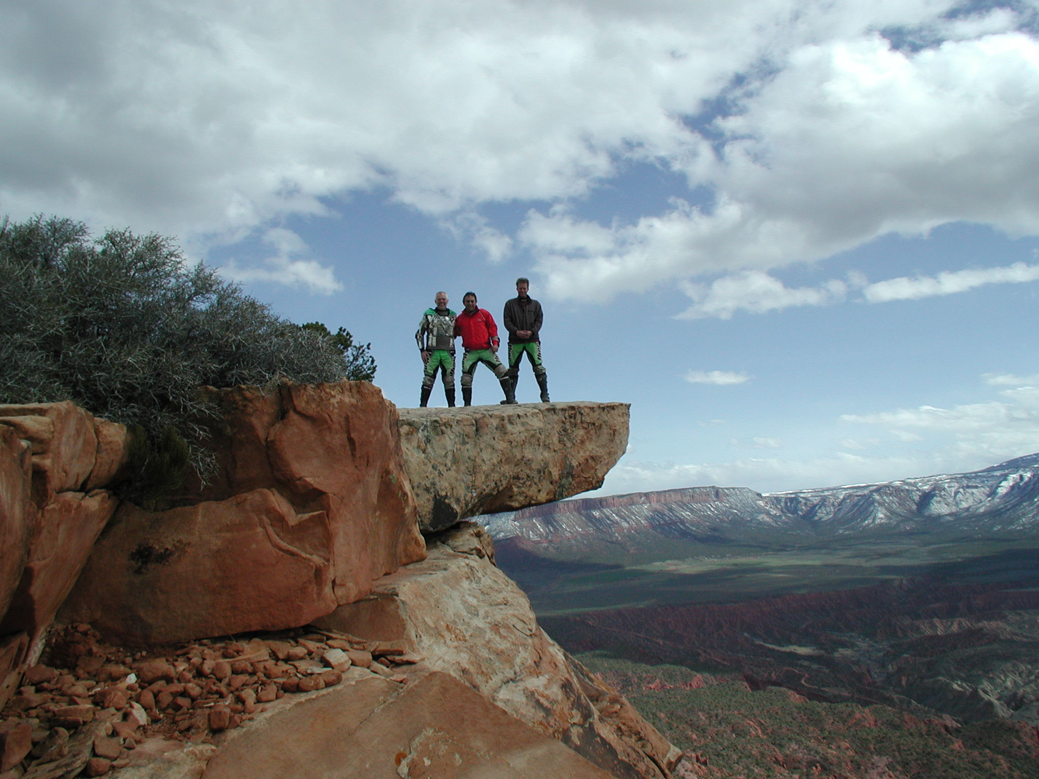 3 men standing on a rock