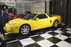 a yellow Acura NSX in the garage