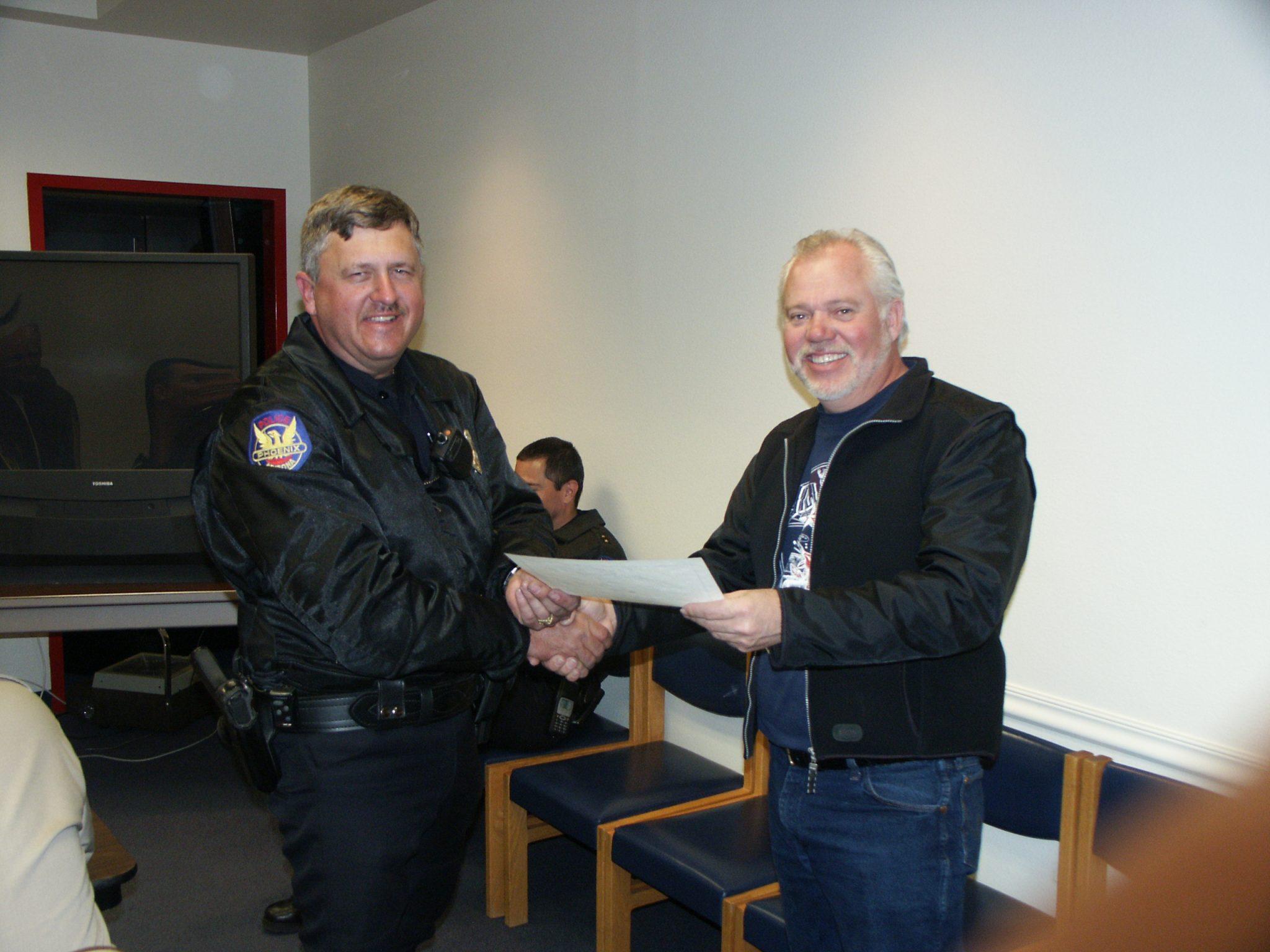Men shaking hands, one is a cop