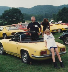 man, young girl and a small yellow car