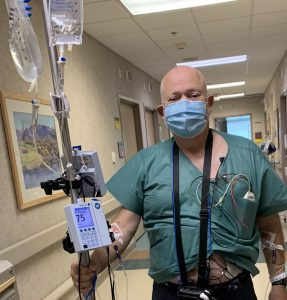 Steve holding his IV bags, wearing monitoring devices