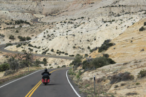 solo motorcycle rider heading into the dry hills